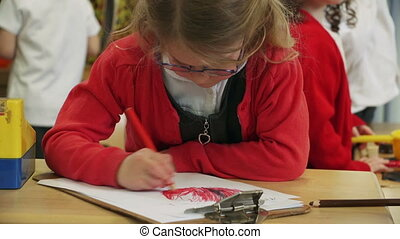 Alone time at nursery - Little girl doing colouring in her...