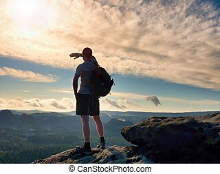 Alone tourist with sporty backpack stand on cliff edge and ...