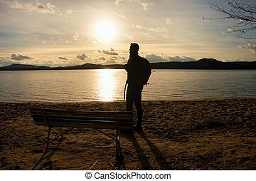 Alone traveler with backpack. Man on sea beach at wooden bench, cold sunny autumn evening