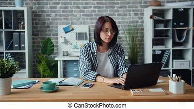 alors, femme, bureau, fonctionnement, ordinateur portable, regarder, appareil photo, portrait, sourire