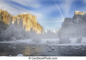 Alpenglow on the granite peaks in Yosemite valley with mist...