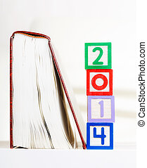 Alphabet block with 2014 besides book