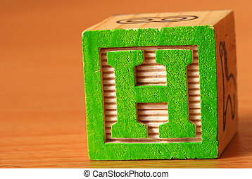 Alphabet block with a green letter H