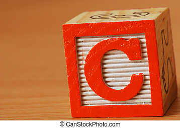 Alphabet block with a red letter C