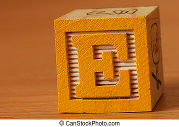 Alphabet block with a yellow letter E