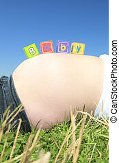 Alphabet blocks spelling BABY on a pregnant belly