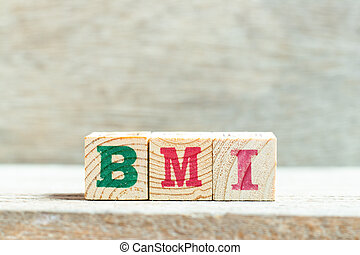 Alphabet letter block in word BMI (abbreviation of body mass index) on wood background