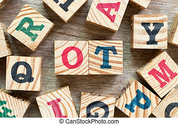 Alphabet letter block in word OT (abbreviation for overtime) with another on wood background