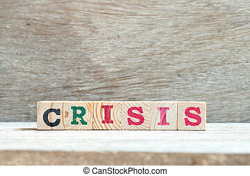 Alphabet letter in word crisis on wood background