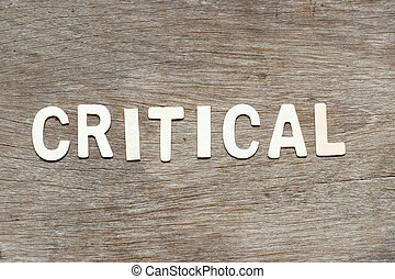 Alphabet letter in word critical on wood background