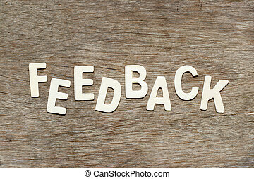 Alphabet letter in word feedback on wood background