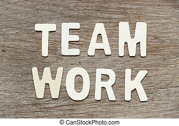 Alphabet letter in word teamwork on wood background