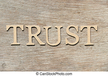 Alphabet letter in word trust on wood background