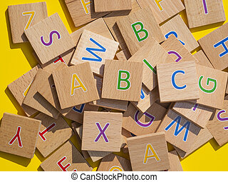 alphabet letters on wooden cubes on yellow background