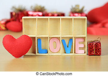 alphabet of LOVE in wooden box near red heart shape and gift box on wooden floor.