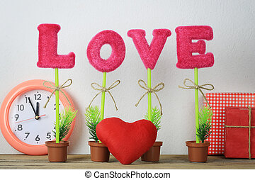 alphabet of love placed on a wooden floor and Red heart near gift box and clock.
