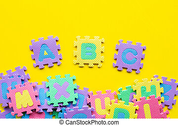 Alphabet puzzle on yellow background.