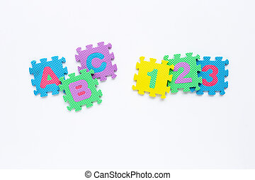 Alphabet puzzle with number puzzle on white background.