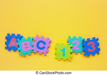 Alphabet puzzle with number puzzle on yellow background.