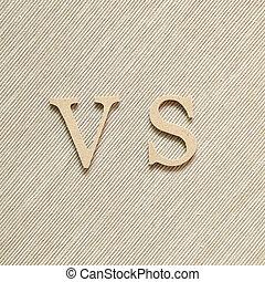 Alphabet VS, versus on brown fabric background