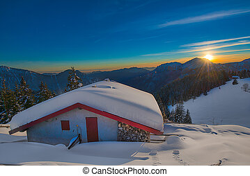 Alpin hut in the snow during sunset