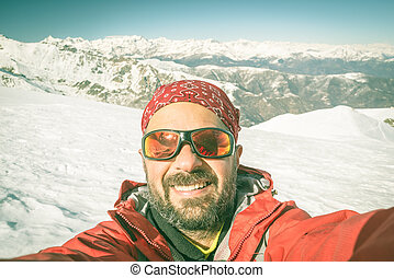 Adult european man taking selfie on snowy slope with the beautiful snowcapped italian Alps in the background. Toned image, old retro touch, desaturated.