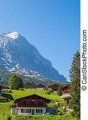 Alpine Chalet on the background of Eiger peak. Grindelwald Switzerland, Europe