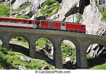Alpine express passing bridge at St. Gotthard Pass in...