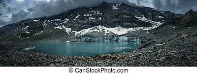 Alpine glacier lake in Swiss Alps - with water and ice in cold blue tones, panoramic shot