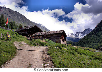 Alpine hut in the Pfossental in South Tyrol, Italy. In background the sumnits of the Oetztal Alps. It's sunny day in summer with blue sky and white clouds.