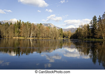 Alpine lake reflection at Brdo near Kranj outdoor park,...