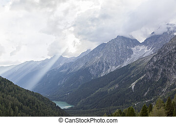Alpine landscape with rocky peaks and lake in mountain valley.