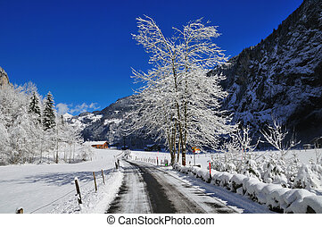 Alpine Road - Snowy road in an alpine valley under a bright ...