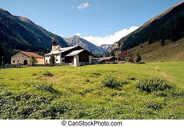 Alpine rural scene seen from a rocky ridge. Hiking in Swiss Alps.