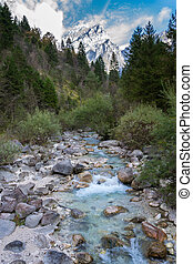 Alpine torrent with a mountain in the background