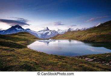 Alpine view of the Mt. Schreckhorn and Wetterhorn. Location Bachalpsee in Swiss alps, Grindelwald valley, Europe.