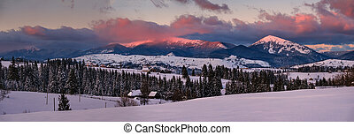 Alpine village outskirts panorama in last evening sunset sun light. Winter snowy hills and fir trees, magnificient and picturesque mountain range in far. Voronenko, Ukraine, Carpathian.