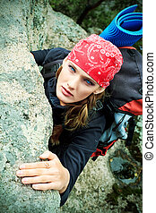 alpinism - Beautiful woman alpinist is climbing on a ...
