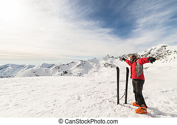 Male adult alpinist with pair of back country ski on the mountain summit. Shot in backlight, stunning panoramic view of the alpine arc. Concept of success and conquering the top.