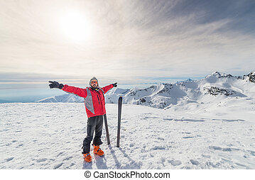 Male alpinist with arms outstretched near pair of back country ski on the mountain summit. Shot in backlight, stunning panoramic view of the alpine arc. Concept of success and conquering the top.