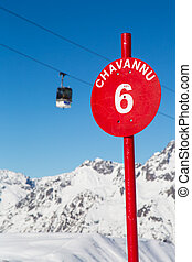Alps in winter - A red slope sign with a ski lift in the ...