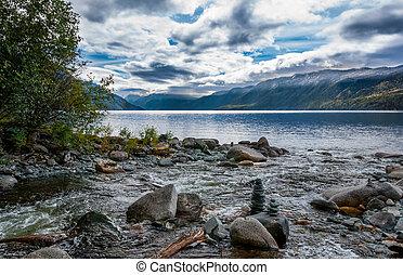 Altai mountains landscape. Balanced stack of stones on the shore of Teletskoye lake. Siberia, Russia