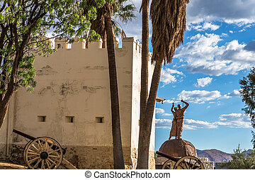 Alte Feste fortress with cannons, palms and independence  monument int the background, center of Windhoek, Namibia