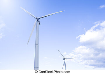 Alternative Energy Concepts. Two Windmills Outdoors Against Blue Sky.