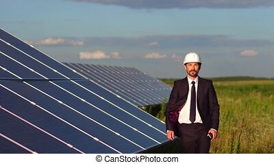 Footage with happy smiling businessman checking work of solar panels in the field.