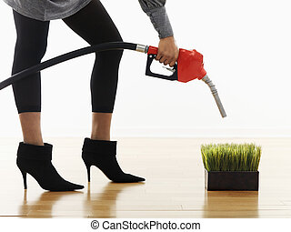 Alternative fuel concept - Woman holding gasoline pump...