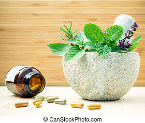 Alternative health care and herbal medicine .Fresh herbs and herbal capsule with mortar and pestle on wooden background. Various herbs rosemary ,sage ,sweet basil leaves and  green mint branch.