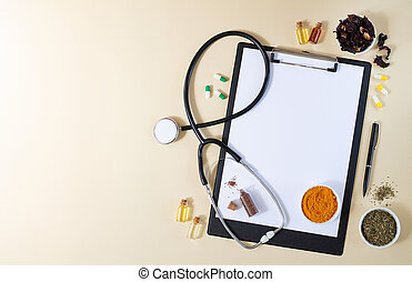 Alternative medicine, nathuropathy or ayurveda concept. Blank clipboard with stethoscope, various healing herbs, spices, capsules and healthy oils on beige table top view