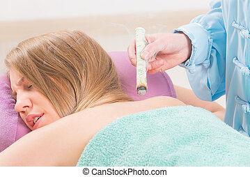Alternative medicine therapist doing moxa treatment