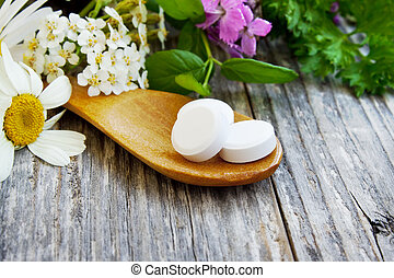 Alternative medicine - wooden spoon with pills with herbs...